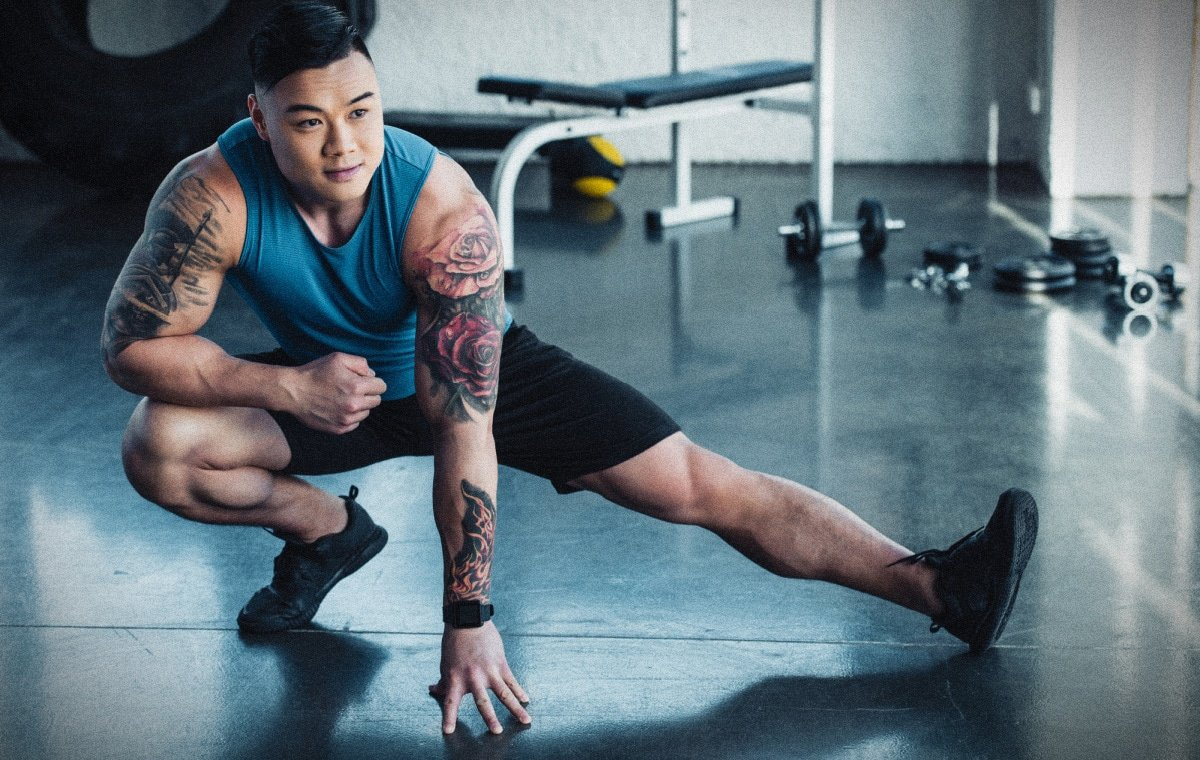 Best Tank Tops for Men Muscular Asian Man with Tattoos Working Out In a Gym