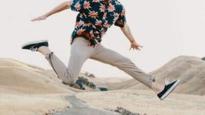 Twill Pants Man Jumping in Mid Air in The Desert Wearing Twill Pantsinos and Floral Shirt With Hands Out