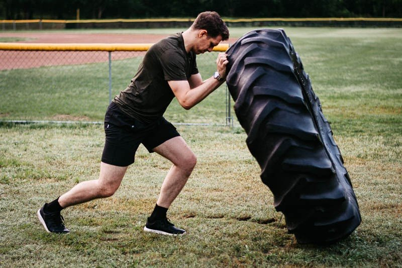 model flipping tire wearing kore workout shorts from vuori