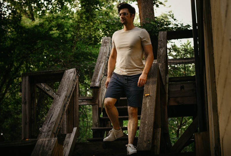 model walking down wooden steps wearing basic man shirt and public rec shorts