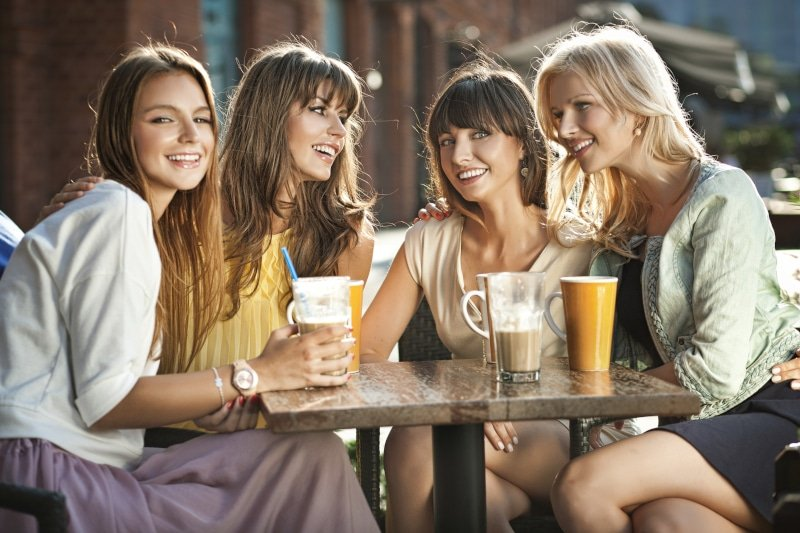 A group of woman sitting together at a coffee shop outside