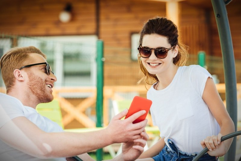 Man showing smart phone to a woman