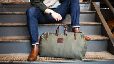 Mens Accessories Stylish Model Sitting on Steps with Weekender Bag and Watch Showing