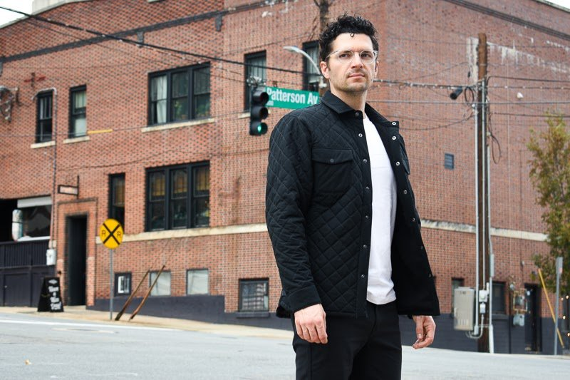 model wearing quilted jacket against brick building