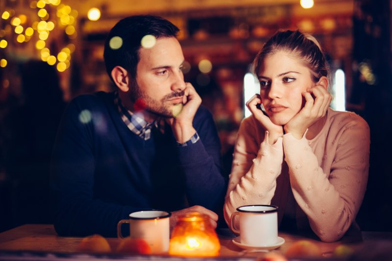 Guy and girl on a date while sad and disinterested