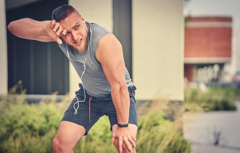 Man wearing headphones and tired from running