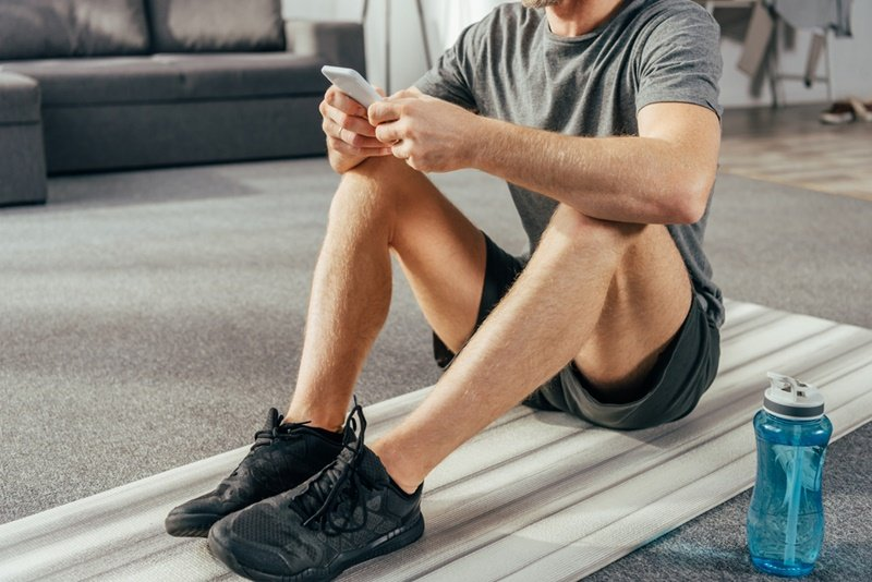 Man doing home workout using phone between sets