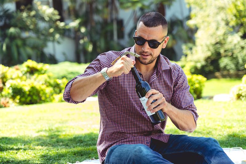 Model drinking wine in park