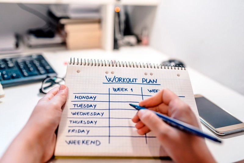 Person Using Workout Plan with Pen in Hand