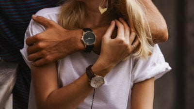 Couple Watches Man and Girlfriend Wearing His and Hers Watches and Hugging